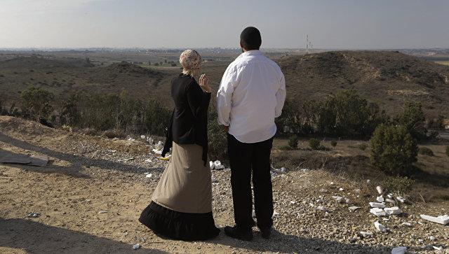 Израильтяне на фоне панорамы Сектора Газа на окраине израильского города Сдерот. Архивное фото