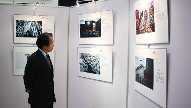 Посетитель на открытии выставки победителей конкурса имени Андрея Стенина в Пекине. 18 декабря 2017