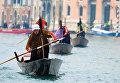 Мужчины в костюме Бефаны плывут по Гранд-каналу в Крещенский сочельник в Венеции