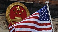 Флаг США на фоне эмблемы Китая в Пекине. Архивное фото