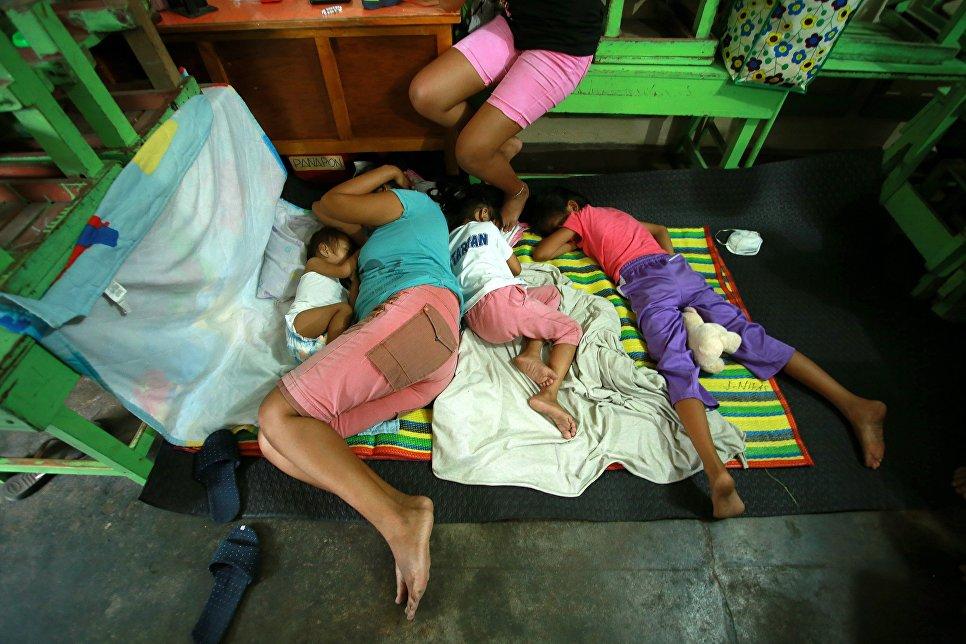 Филиппинцы спят во временном убежище после эвакуации из своих домов из-за извержения вулкана Майон в городе Камалиг, провинция Албай. 15 января 2018 года