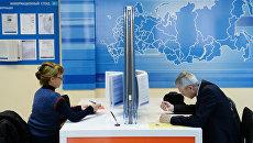 Посетители заполняют документы в инспекции Федеральной налоговой службы РФ