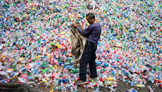 Китайский рабочий, сортирующий пластиковые бутылки для переработки, на окраине Пекина. Архивное фото
