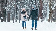 Молодая пара во время прогулки в парке зимой
