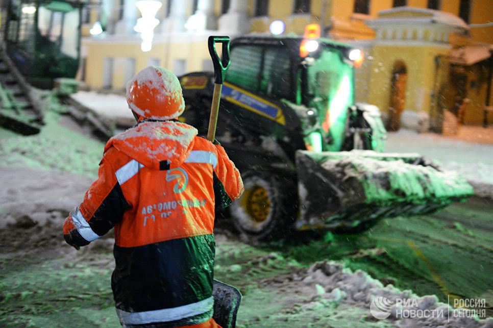 Сотрудники коммунальных служб убирают снег на улице в Москве. 31 января 2018