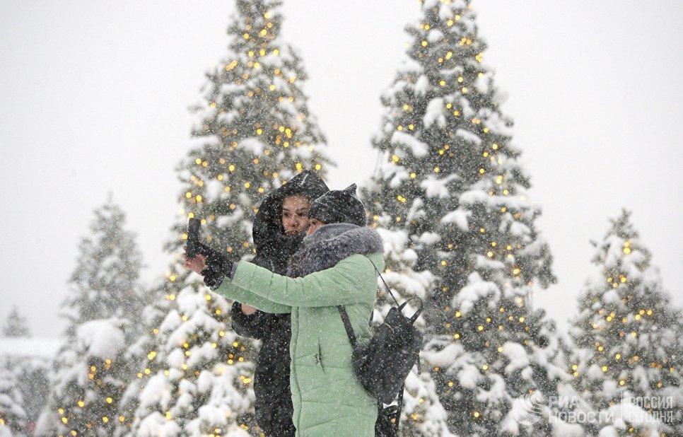Девушки фотографируются во время снегопада на Манежной площади в Москве. 4 февраля 2018