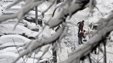Сотрудники коммунальных служб убирают снег на дороге в Москве