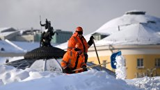 Сотрудники коммунальных служб убирают снег на Манежной площади в Москве