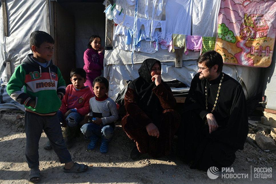 Глава российской делегации межрелигиозной рабочей группы Совета по взаимодействию с религиозными объединениями при президенте РФ иеромонах Стефан (Игумнов) во время раздачи гуманитарной помощи в палаточном лагере для сирийских беженцев в долине Бекаа в Ливане