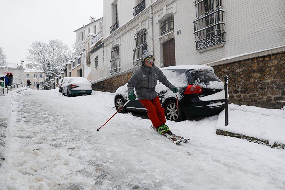 Мужчина съезжает на лыжах по одной из улиц Монмартра после снегопада в Париже