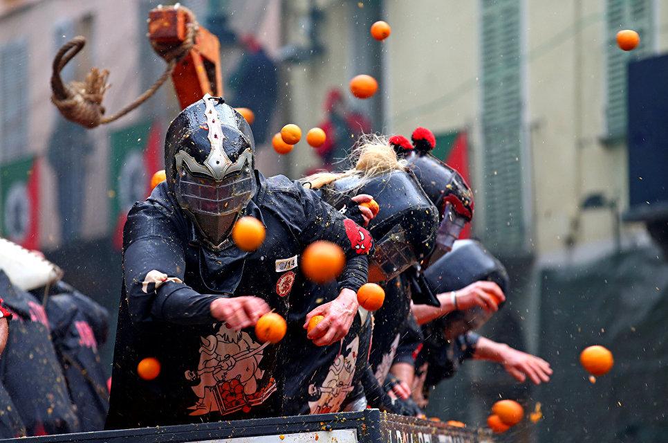 Участники ежегодной битвы апельсинами в Иврее, Италия