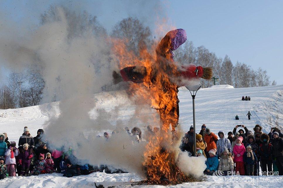 Сжигание чучела во время праздничных гуляний, посвященных проводам Широкой Масленицы в парке наукограда Кольцово в Новосибирской области. 17 февраля 2018