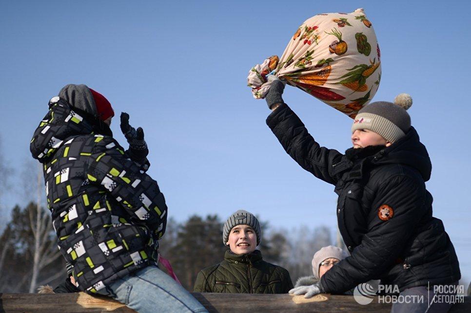 Участники традиционной забавы бой мешками во время проводов Широкой Масленицы в парке наукограда Кольцово в Новосибирской области. 17 февраля 2018