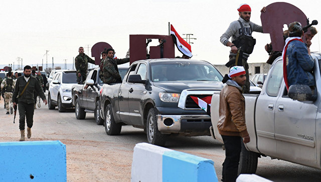 Курдские бойцы приветствуют конвой просирийских правительственных сил, прибывающих в сирийский Африн. 20 февраля 2018