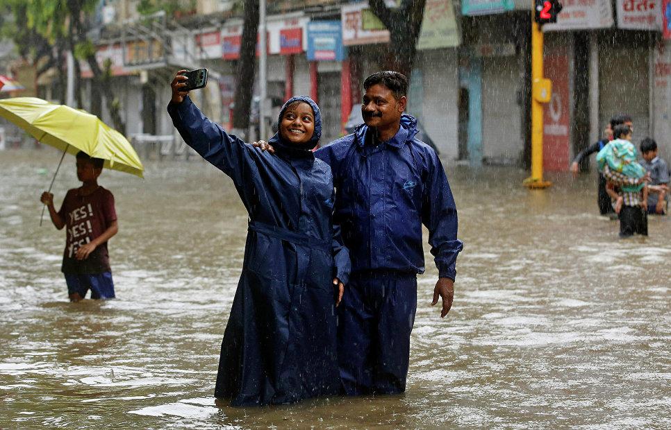 Жители Индии делают селфи на затопленных улицах во время дождя в Мумбаи. 2015 год