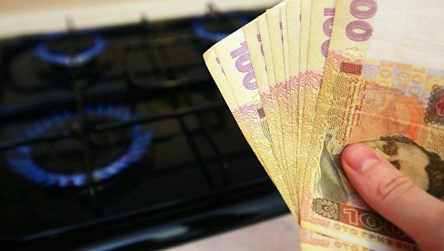 Горящая газовая конфорка и денежные купюры Украины. Архивное фото