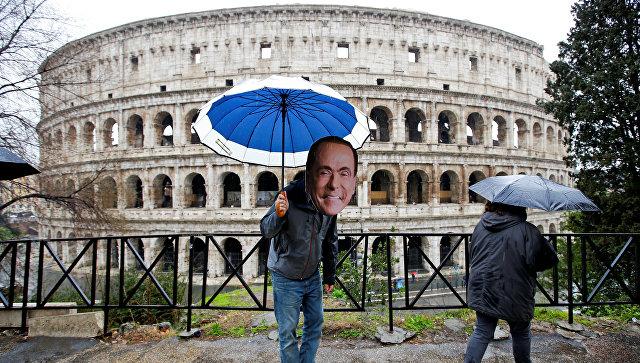 Активист в маске лидера партии Вперед, Италия Сильвио Берлускони на следующий день после парламентских выборов в Риме. 5 марта 2018