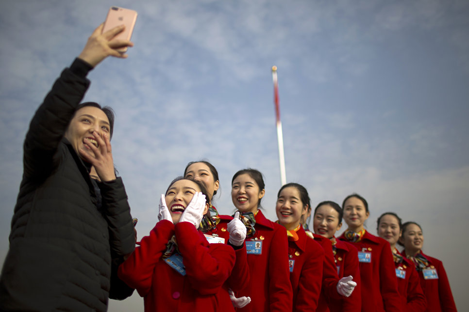 Девушки делают селфи во время открытия сессии Национального народного конгресса Китая в Большом зале народных собраний в Пекине