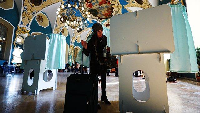 Девушка голосует на выборах президента РФ на избирательном участке на Казанском вокзале в Москве. 18 марта 2018