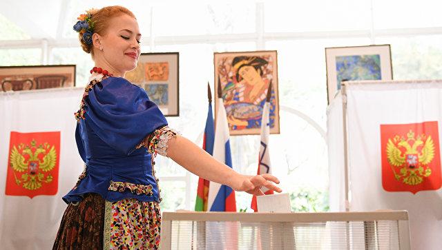 Девушка в национальном костюме голосует на выборах президента РФ в Сочи