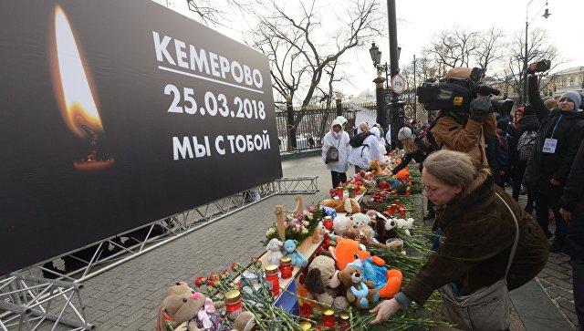 Люди возлагают цветы к мемориалу на Манежной площади в Москве в память о погибших в кемеровском торговом центре Зимняя вишня