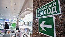Указатель и знак Запасный выход в торгово-развлекательном центре