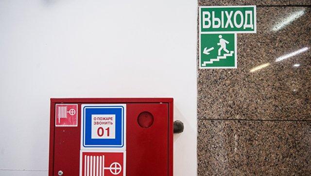 Пожарный шкаф и указатель направления эвакуации при пожаре. Архивное фото