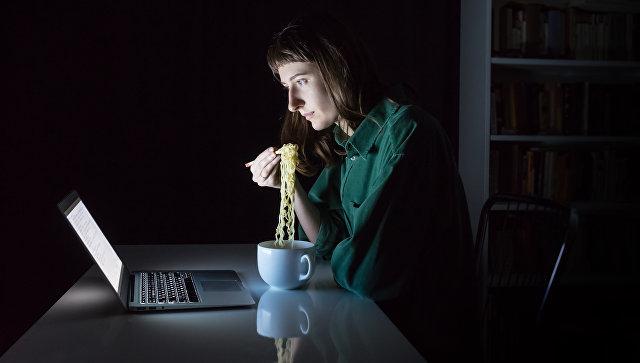 Девушка ест лапшу быстрого приготовления перед экраном ноутбука