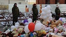 Охранники возле стихийного мемориала из цветов и игрушек в Кемерово. 5 апреля 2018