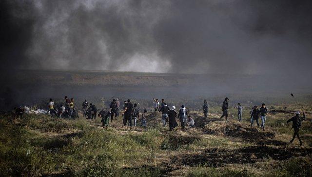 Палестинские протестующие во время столкновений с израильскими военными на границе сектора Газа и Израиля