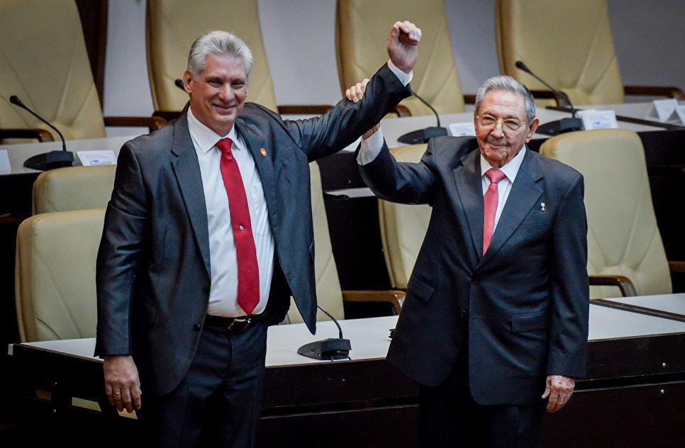 Рауль Кастро поднимает руку новому президенту Кубы Мигелю Диас-Канелю после того, как он был официально назначен Национальным собранием в Гаване. 19 апреля 2018 года