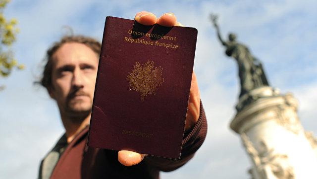 Мужчина с паспортом Франции на фоне статуи Республики в Париже