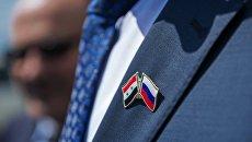Значок с изображением флагов России и Сирии на пиджаке участника церемонии высадки оливковых деревьев в честь российско-сирийской дружбы высадили в Ялте