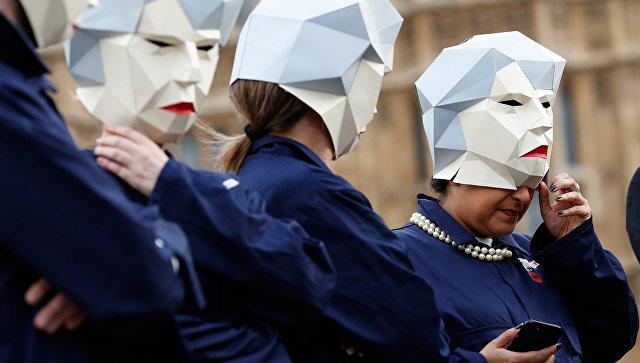 Участники акции протеста в Лондоне в масках, изображающих Терезу Мэй. Архивное фото