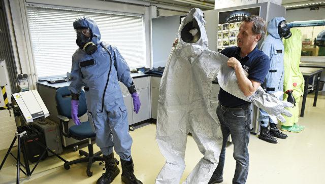 Сотрудник ОЗХО демонстрирует защитный костюм, использовавшийся экспертами во время расследования отравления Сергея Скрипаля в Великобритании. Архивное фото