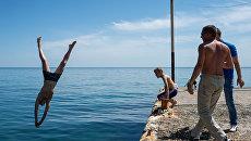 Отдыхающий прыгает с пирса в море в Новом Свете
