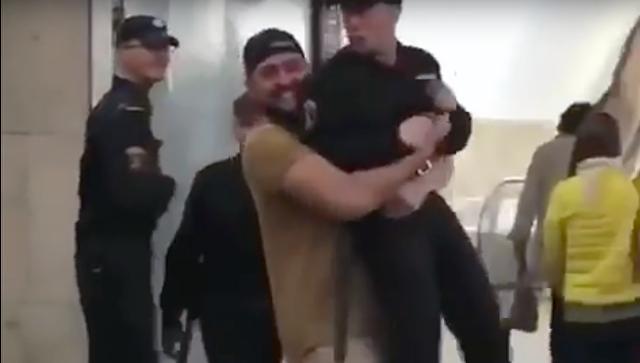 Стоп-кадр с видео, где мужчина несет сотрудника Росгвардии в руках по вестибюлю станции Сухаревская