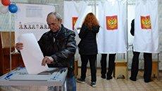 Мужчина опускает бюллетень во время голосования на выборах президента России на избирательном участке в Крыму