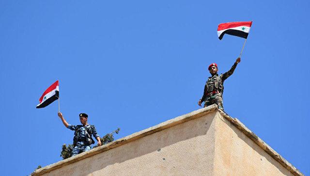 Сирийские военные с флагами в освобожденном от боевиков населенном пункте в провинции Хомс. Архивное фото