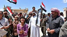 Люди в населенном пункте, освобожденном от боевиков, в сирийской провинции Хомс. Архивное фото