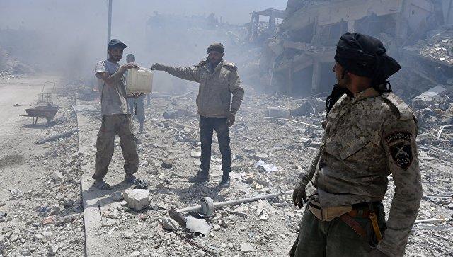 Мужчины на улице в освобожденном лагере палестинских беженцев Ярмук на юге Дамаска