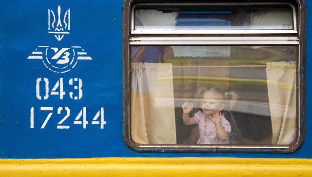 Девочка в поезде, отправляющемся с железнодорожного вокзала в Киеве, Украина. Архивное фото