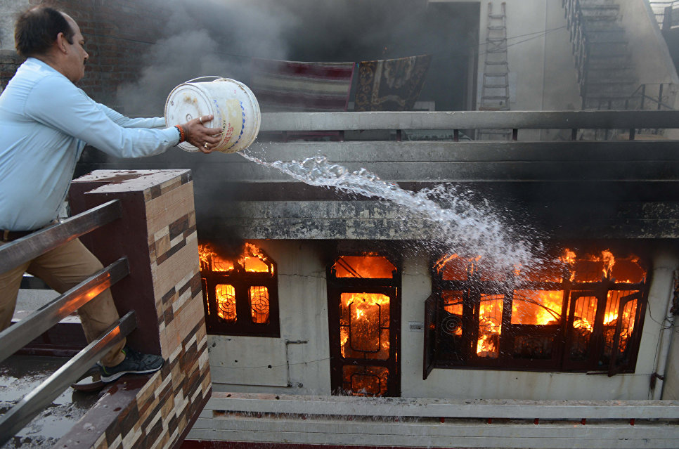 Мужчина пытается потушить пожар в магазине электротоваров в Амритсаре, Индия
