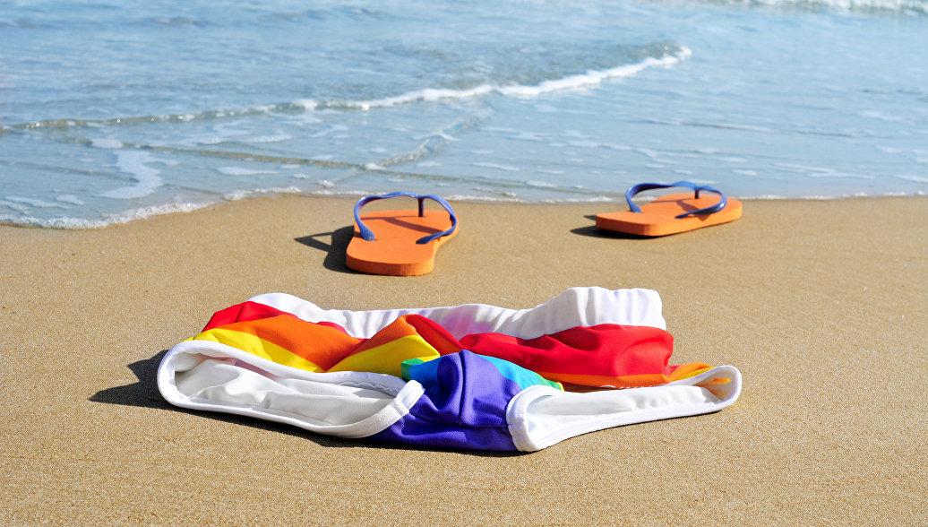 Купальник и шлепанцы на песке пляжа