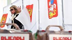 Девушка во время голосования на выборах. Архивное фото