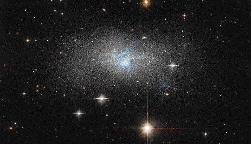 Снимки карликовой галактики IC 4870 c нитями голубого газа в центре