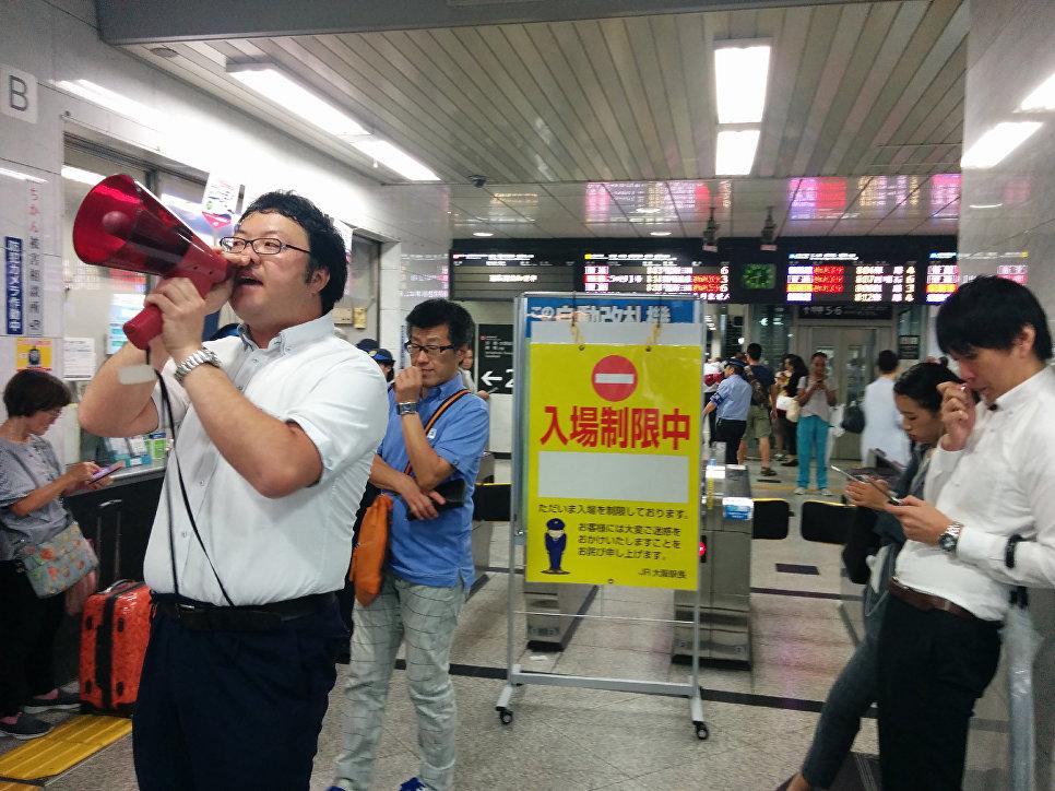 Сотрудник станции делает объявление пассажирам после землетрясения в Осаке
