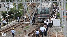Эвакуация пассажиров из поезда после землетрясения в Осаке, Япония. 18 июня 2018