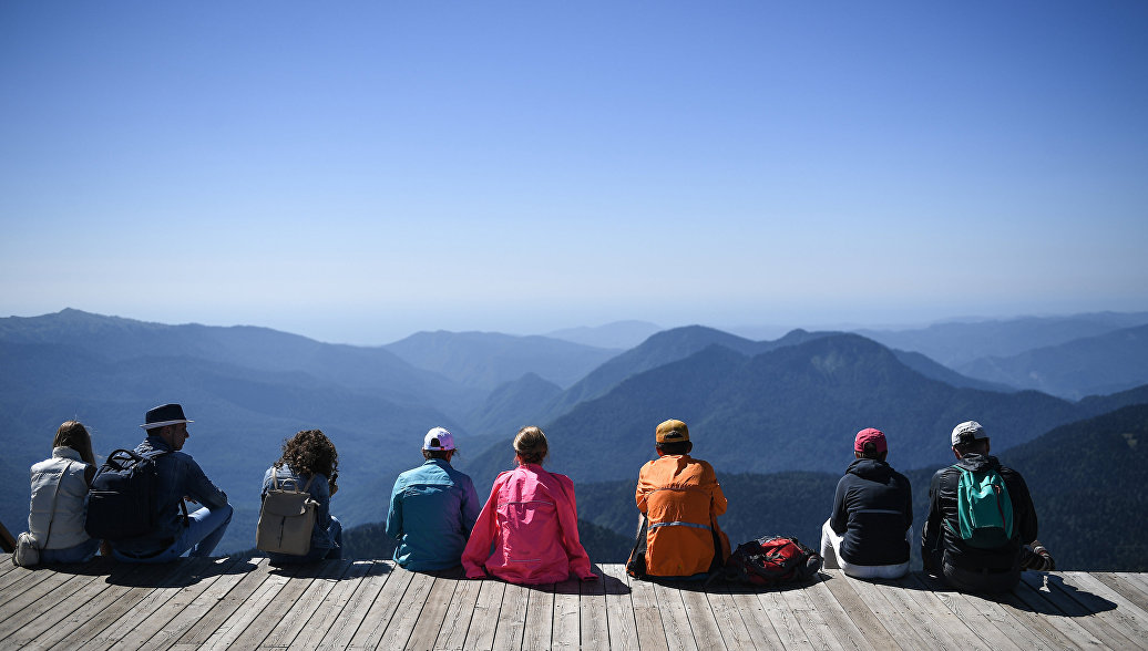 Туристы на обзорной площадке на вершине Роза Пик на высоте 2320 метров на горном курорте Роза хутор в Красной поляне.