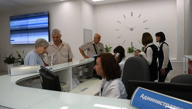 Посетители у регистратуры поликлиники. Архивное фото